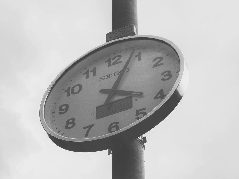 Straßenuhr welche 16:04 Uhr anzeigt, in einer schwarz-weiß Photographie.